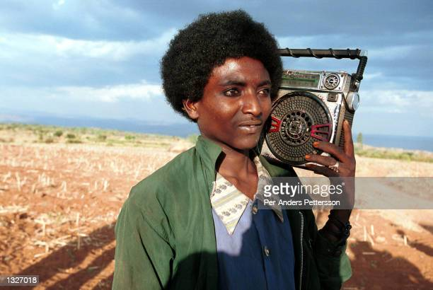 A young man plays contemporary music on his radio February 8 2001 during a wedding ceremony for a young couple in Erer Valley in rural eastern...