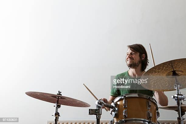 young man plays drums with enjoyment - drum kit stock pictures, royalty-free photos & images