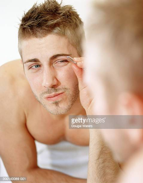 Young man plucking eyebrows with tweezers in mirror, close-up