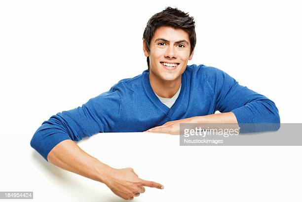 Young Man Pointing at a Blank Wall - Isolated