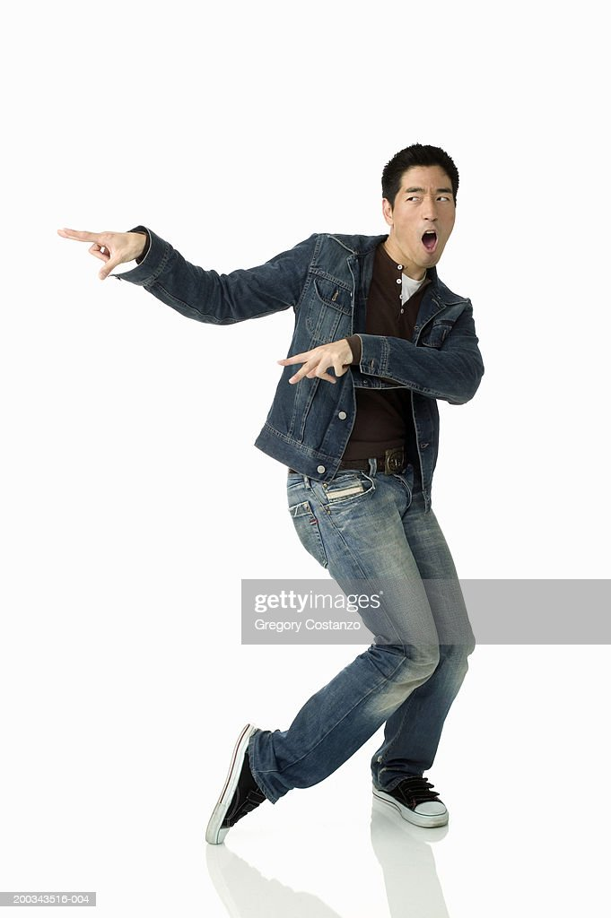 Young man pointing fingers, mouth open : Stock Photo