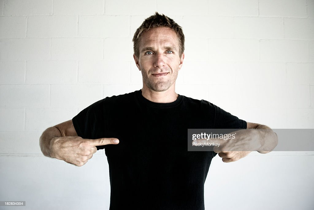 Young Man Pointing to Black T-Shirt Copy Space : Stock Photo