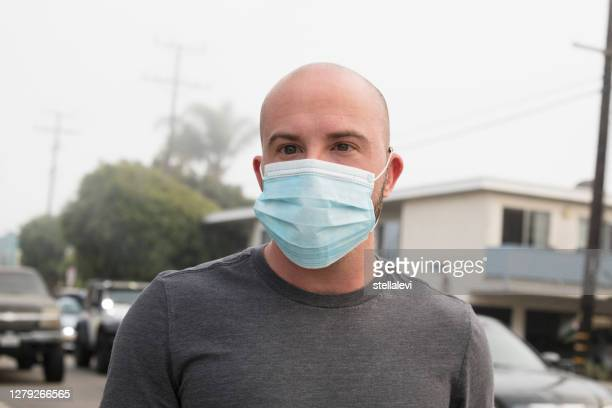 young man portrait outdoors with face mask for protection - stellalevi stock pictures, royalty-free photos & images