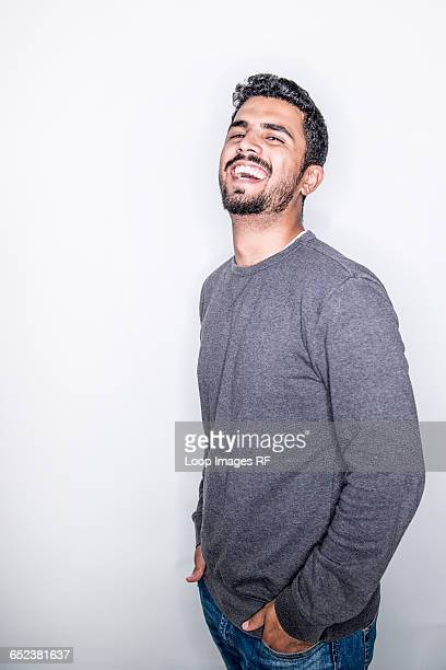 A young man posing in a studio laughing