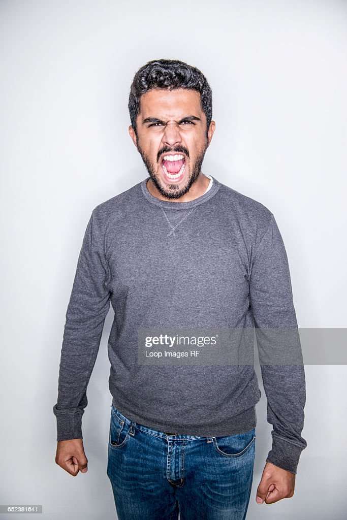 A young man posing in a studio looking angry : Stock Photo