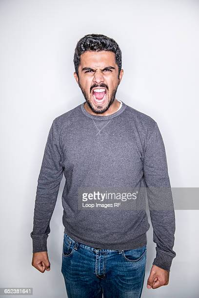 a young man posing in a studio looking angry - anger stock photos and pictures