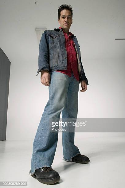 young man posing in studio, low angle view - posing shoes stock pictures, royalty-free photos & images