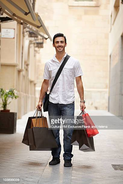 Young man posing with shopping bags