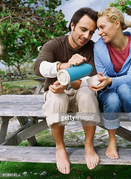 Young man pouring a beverage from a flask for his partner