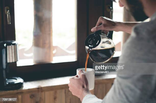 young man pouring coffee into cup at home - morgen stockfoto's en -beelden