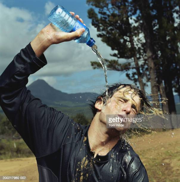 young man pouring water on self from bottle, washing mud off face - ritemprarsi foto e immagini stock