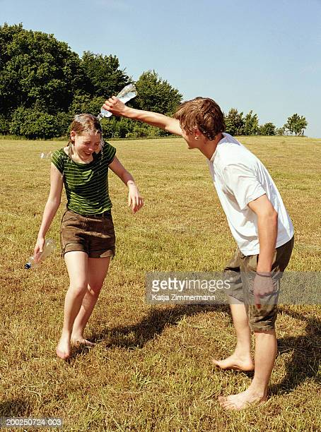 young man pouring water over young woman in field, woman laughing - wet t shirts fotografías e imágenes de stock