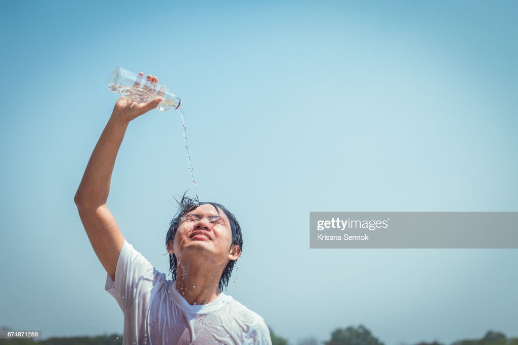 Young man pouring water : Stock Photo