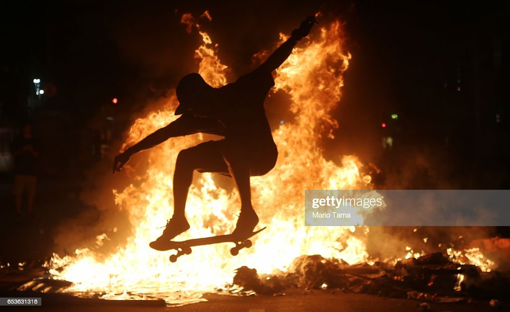 A young man practices a skateboarding move in front of a fire set by protestors following a demonstration against proposed federal government reforms on March 15, 2017 in Rio de Janeiro, Brazil. Protestors rallied nationwide, mostly peacefully, against proposed rules tightening pensions as the country continues to suffer through a financial and political crisis.