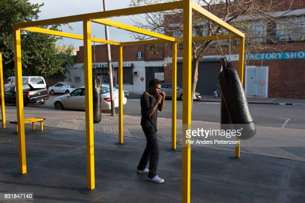 A young man practices boxing at an outdoor gym outside a newly refurbished apartment building in Maboneng district on March 15 2016 in downtown...