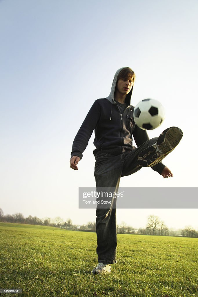 A Young man practices his football skills : Stock Photo