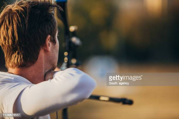 young man practicing archery - curved arrows stock photos and pictures