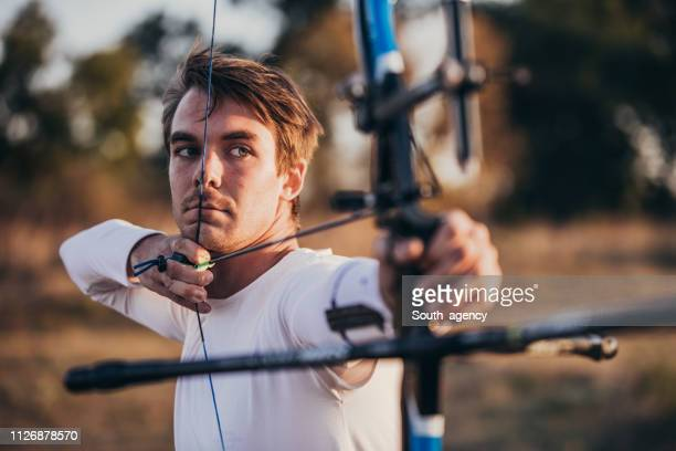 young man practicing archery - archery stock pictures, royalty-free photos & images