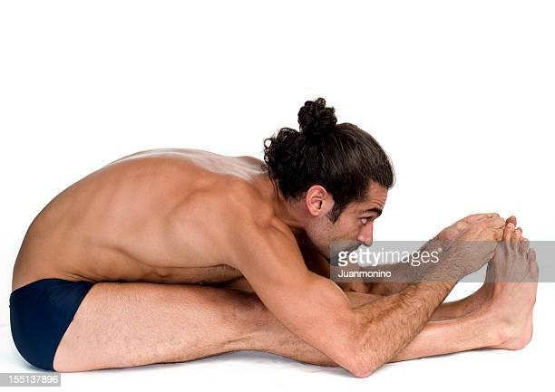 Young man practicing bikram hot yoga Paschimotthanasana position