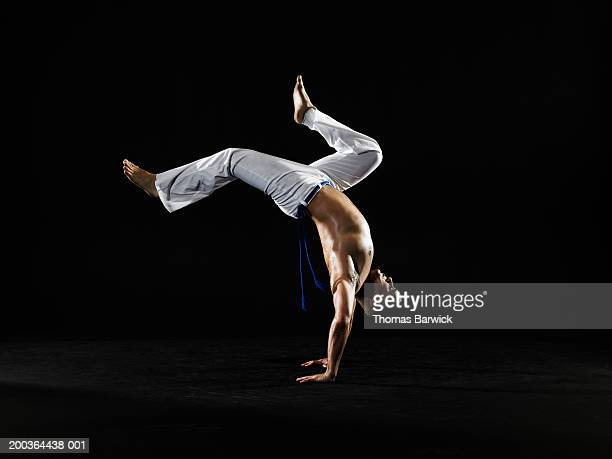 Young man practicing capoeira, bending over backwards, side view