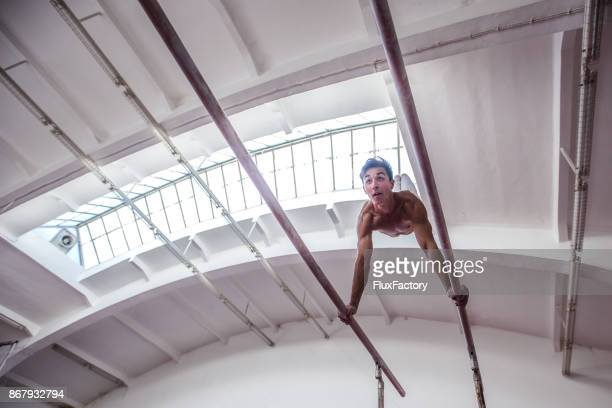 young man practicing gymnastics - parallel bars gymnastics equipment stock photos and pictures