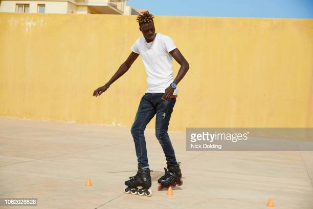 young man practicing his inline skating skills - cabo verde fotografías e imágenes de stock