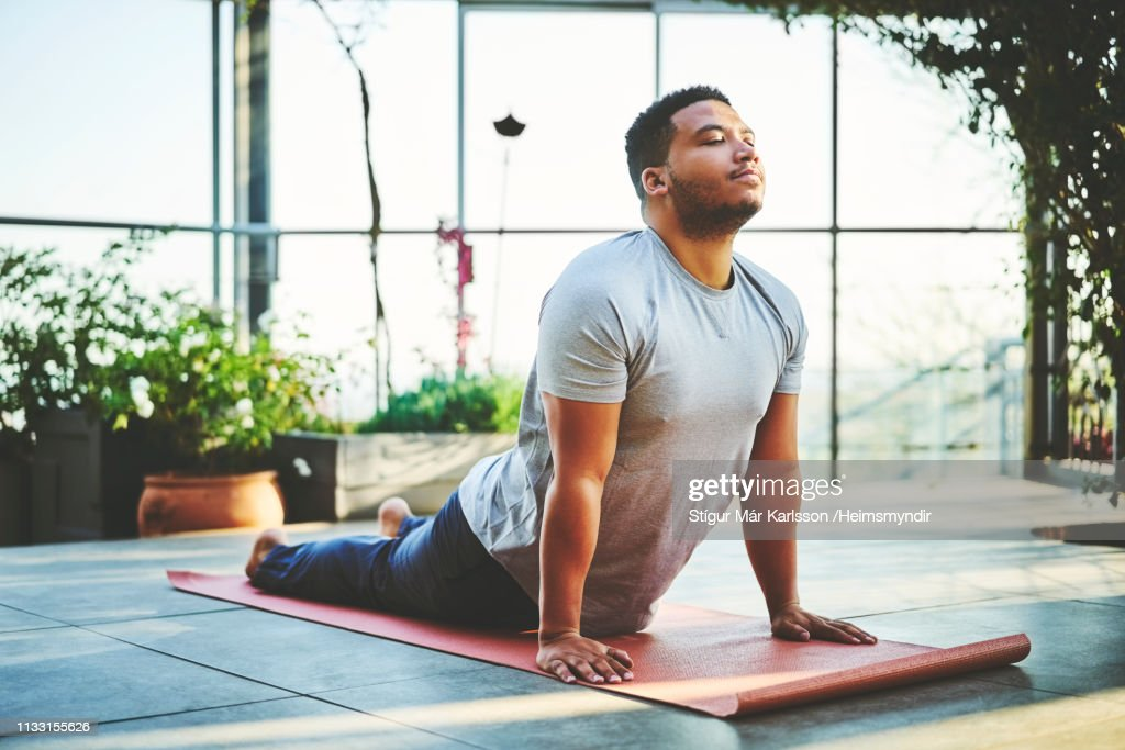 Young man practicing Upward Facing Dog Pose : Stock Photo