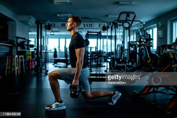 young man practicing walking lunge with kettle bell - squatting position stock pictures, royalty-free photos & images