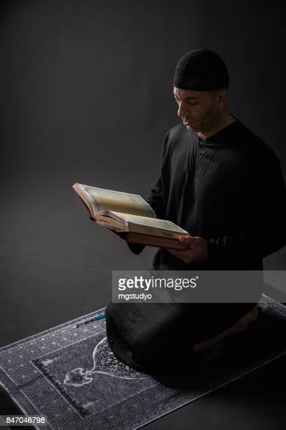 Young man praying  over black backround