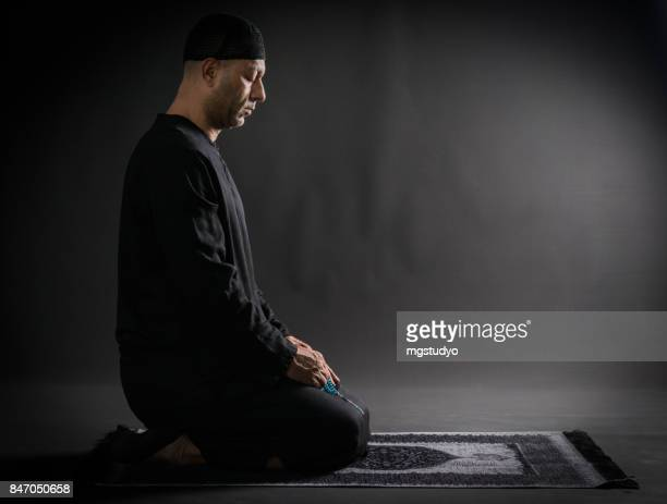 young man praying  over black backround - muslim praying stock pictures, royalty-free photos & images