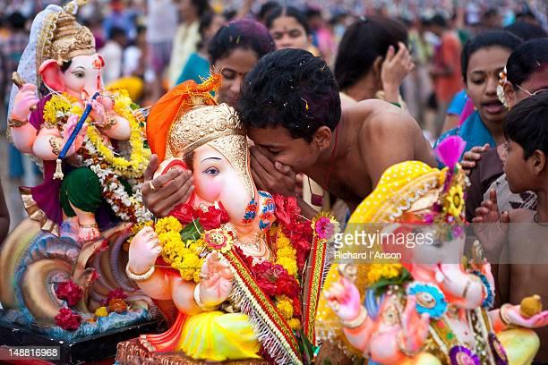 Young man praying to Ganesh statue on Chowpatty Beach during Ganesh Chatsuri festival.