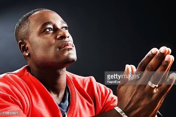 Young man prays devoutly, his hands folded
