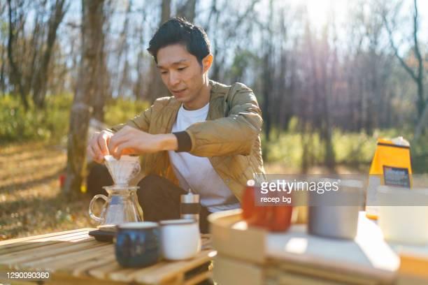冬の寒い天候の朝に若い男がコフェを耕す - キャンプ 1人 ストックフォトと画像