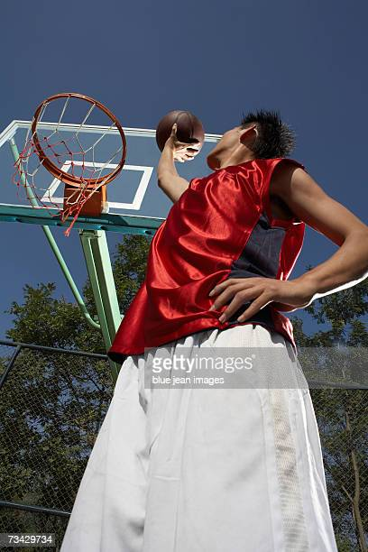 A young man prepares to shoot the ball one handed, shot from below.