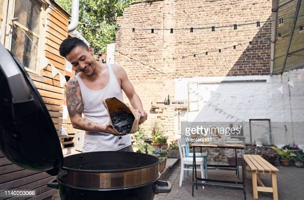 young man preparing babecue grill, using charcoal - vest stock pictures, royalty-free photos & images