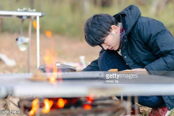 冬のキャンプ場で朝食を準備している若い男 - キャンプ 1人 ストックフォトと画像