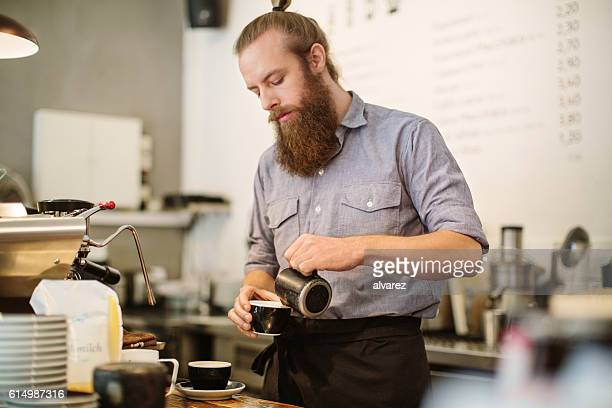Young man preparing coffee at cafe counter