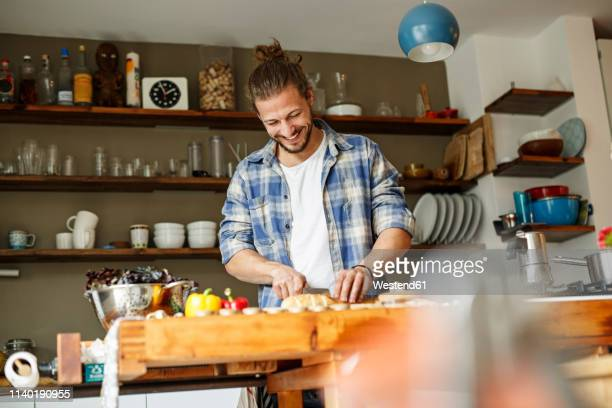 young man preparing food at home, slicing bread - kochen stock-fotos und bilder