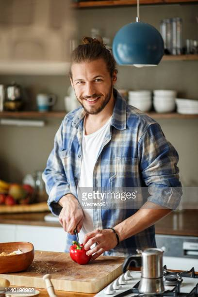 young man preparing food at home, slicing vegetables - man bun stock pictures, royalty-free photos & images