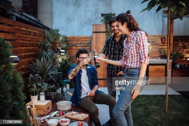 junger mann bereitet essen für seine freunde vor - gartenparty stock-fotos und bilder