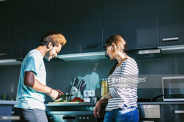 Young man preparing food in the kitchen while woman watching him