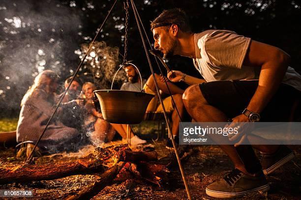 友人とキャンプしながら食べ物を準備している若い男。 - 大釜 ストックフォトと画像