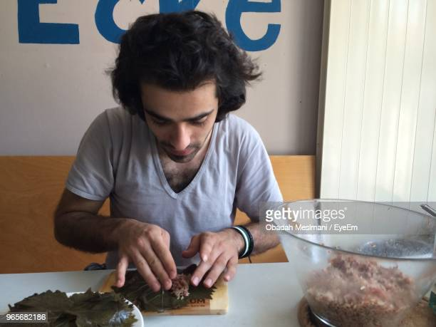 young man preparing food while sitting on table - dolmades stock pictures, royalty-free photos & images