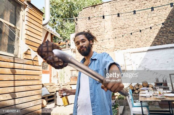 young man preparing meat on a barbecue grill in a backyard - stolz stock-fotos und bilder