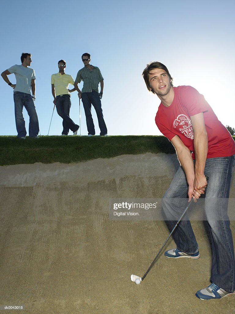 Young Man Preparing to Take a Shot in a Sand Pit with Friends Standing in the Background : Stock Photo