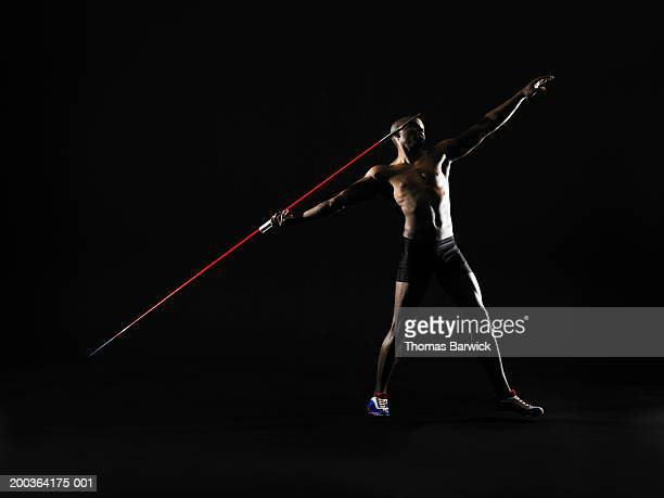 Young man preparing to throw javelin, side view