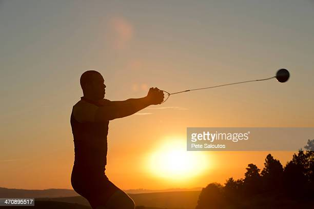 Young man preparing to throw the hammer at sunset