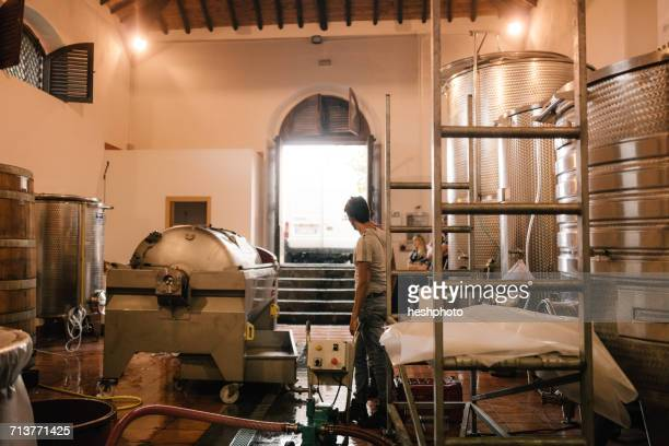 young man preparing vineyard vat for harvested grapes - heshphoto photos et images de collection