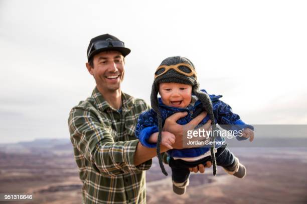 A young man pretending to fly his baby in the air.