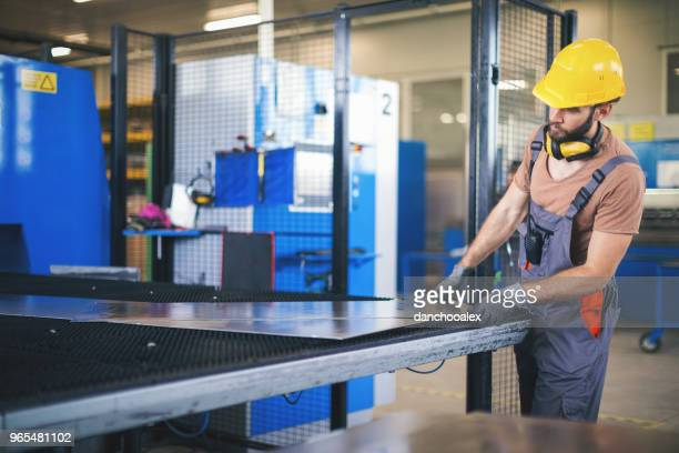 Young man processing metal plates in factory